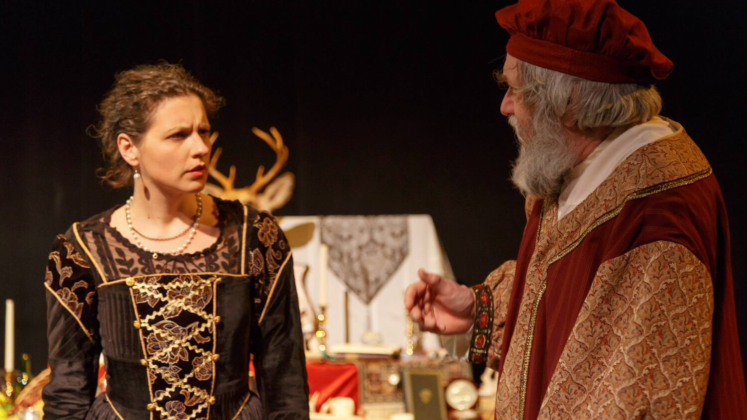 Two actors perform in Richard II. One woman in a black and gold dress looks at a man whose back is to the camera.