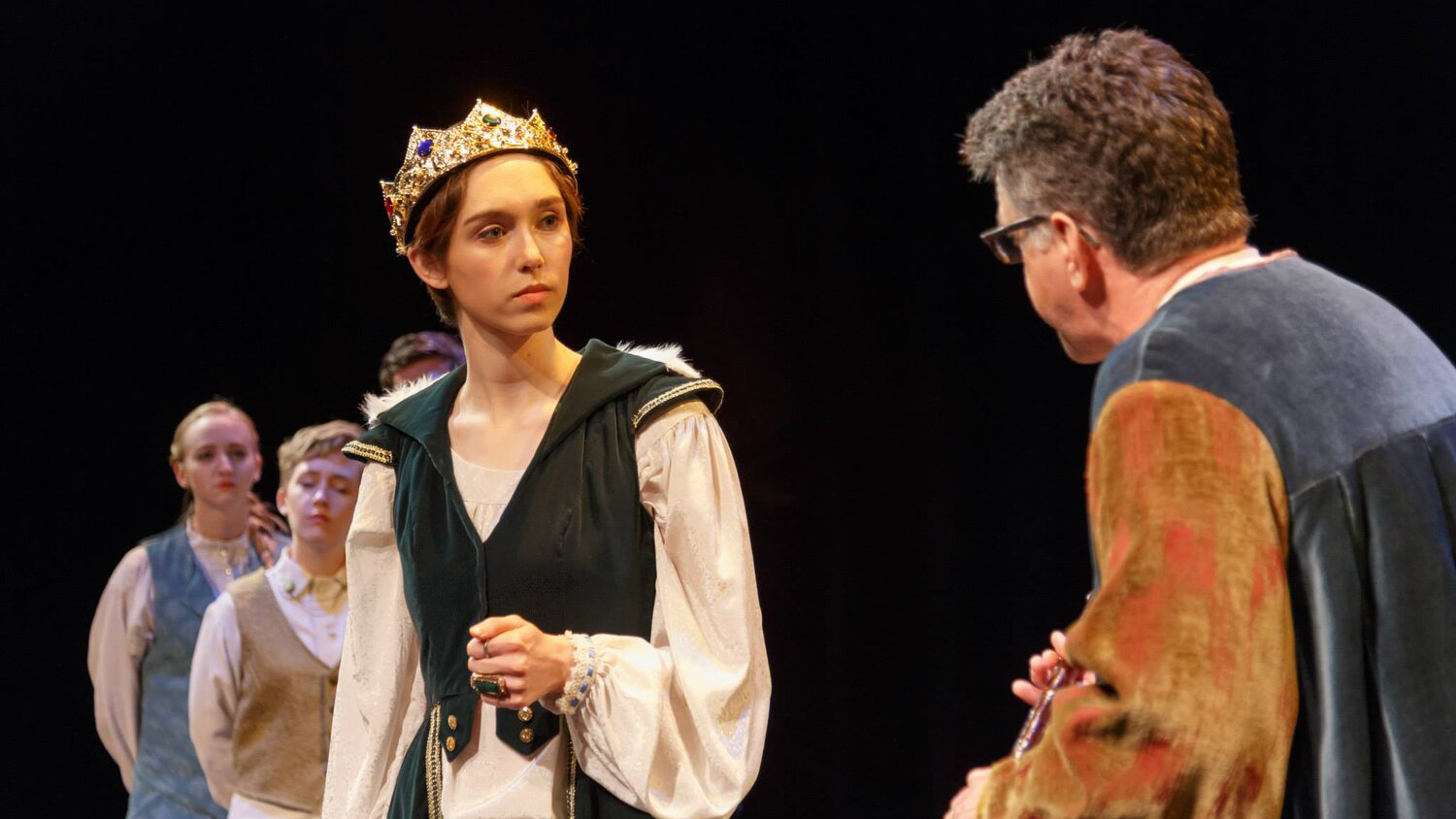 Actors perform in Richard II. One faces the camera wearing a crown.