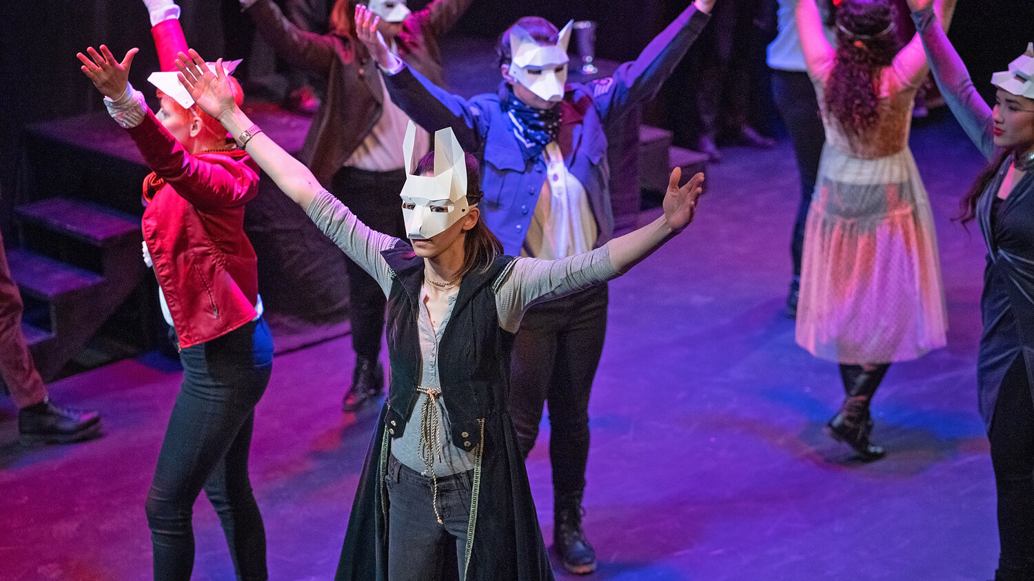 Several actors performing in Romeo and Juliet are wearing white animal-like masks with ears pointing up. Their arms are in the air.