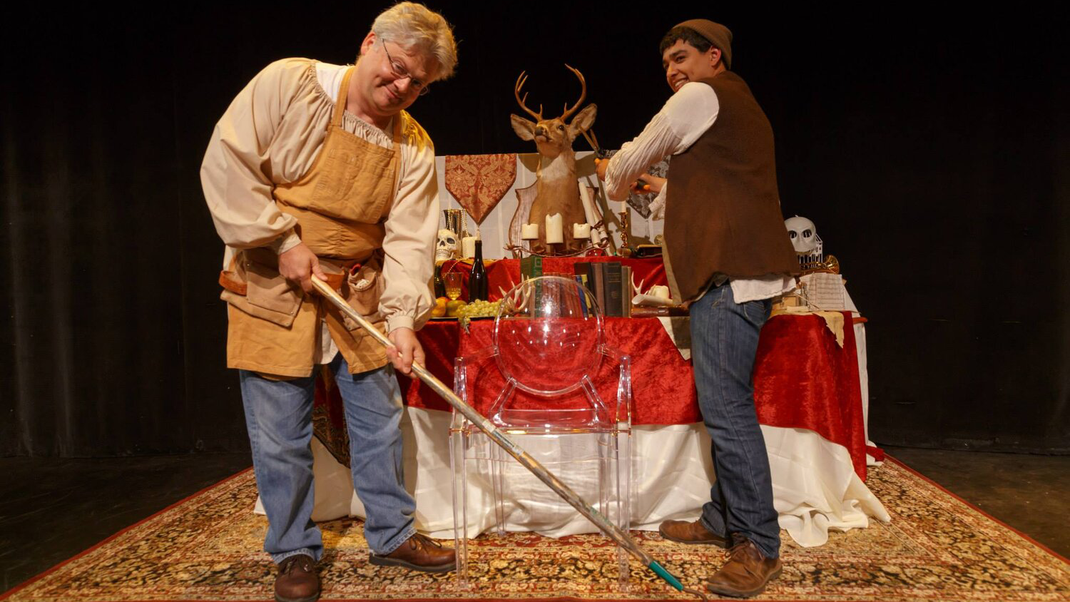 Actors playing gravediggers in Richard II standing in front of a table and clear plastic chair. One is holding a gardening tool.