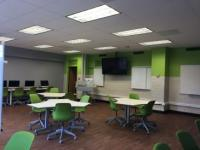 View of modular tables and front of classroom in 312 Denney Hall