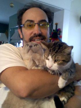 Bob Eckhart holding two cats in what looks to be his home.